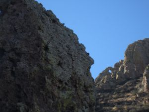 Needle's Eye natural arch (lower right in photo), looking back towards the ridge line from upper Windmill Canyon