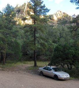 The mighty Camry parked below dawn-illuminated cliffs at the campground.